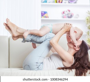 concept of motherhood:happy mother playing with one year old baby in the room for children