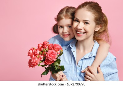 concept of mother's day. mom and child girl with flower on colored background