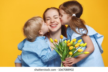 concept of mother's day. mom and children   with flower on colored yellow background