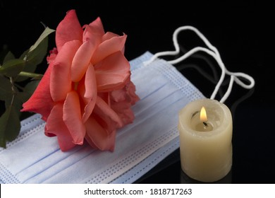 Concept of mourning for covid-19 . Red roses and burning candle over black background