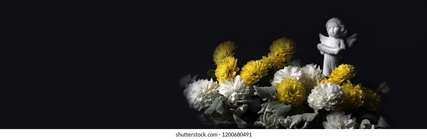 The concept of mourning. White and yellow flowers on a dark background and angel. We remember, we grieve. Selective focus, place for text. Banner