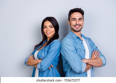 Concept of multiethnic cooperation and friendship. Attractive delightful hispanic woman in denim clothes and handsome causasian smiling man in jeans shirt are standing back to back against  background
