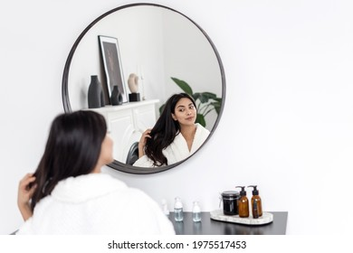Concept of natural beauty and haircare treatment at home. Young asian woman in bathrobe sitting behind makeup table in white modern bathroom, looking at mirror reflection, touching healthy brown hair.