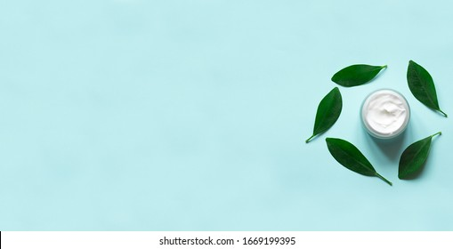 Concept of natural beauty products. With white  cream for skin care on a pastel blue background with green leaves. Top view and copy space