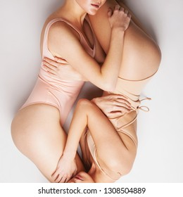 Concept of natural female beauty. Two beautiful women lying on light background