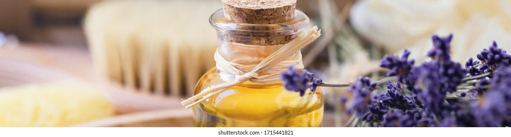 Concept of natural organic ingredients in cosmetology and home beauty treatment. Bottle of essential oil, lavender flowers, bath accessoires, wooden body brush. Close up, banner format