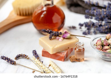 Concept of natural organic spa products, decor for bath. Home body treatment. Handmade herbal soap, organic oil in glass bottle, lavender, brush, towels. Atmosphere of relax, serenity and pleasure.