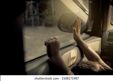 Concept Negligence, forgetting small children in the car :  little girl is trapped inside the car alone, using the glass door handle of the car and no one is paying attention, bowing in sadness.