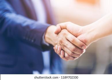 談判業務和握手手勢人們連接交易的概念。商人緊密握手與合作夥伴或客戶在現代城市背景,公平競爭。
