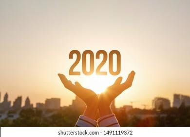Das Konzept neu 2020 Jahr. Hands-Show 2020 auf dem Hintergrund des Sonnenuntergangs.