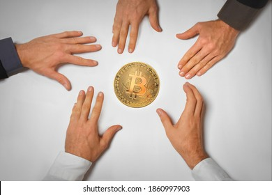 Concept of a new bitcoin hype with five hands reaching for a bitcoin coin