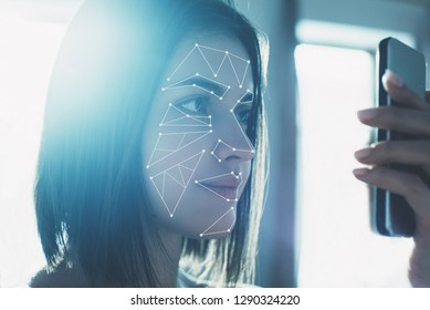 The concept of a new face recognition technology on a polygonal mesh. Young modern girl with a smartphone in his hands.
