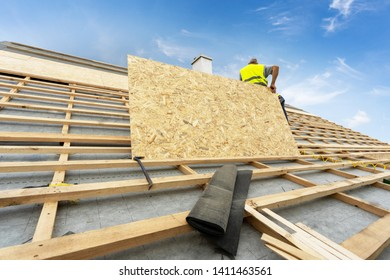 Concept of new framework house. Mature and professional specialist standing on repairing, fixing rooftop of new modern building construction. Man holding in hands wooden, plywood or osb panel