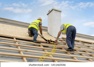Concept of new framework house.Two qualified, unrecognizable and mature builder working on roof top of new modern building construction. Workman holding osb panel or plywood cover on hands