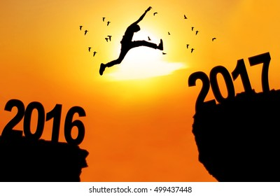 Concept of New Year 2017. Silhouette of a young man jumping between 2016 and 2017 above a cliff