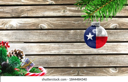 Concept of New Year and Christmas, on a wooden background, Christmas tree branches and a Christmas toy with the flag State of Texas.