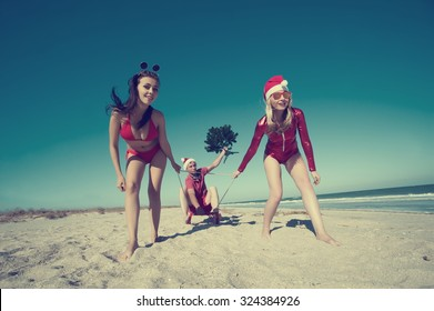 Concept: New Year on the beach. Two girls in Christmas costumes dragging sleds on the beach with a guy
