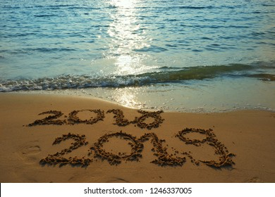 Concept New Year's Eve 2018 Welcomes 2019, writing on the sand beach during sunset hour.