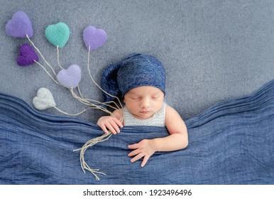 Konzept Neugeborenen Baby-Studio Fotoaufnahme. Kleinkinder, die mit einer blauen Decke schlafen und Strickspielzeug in Herzform halten