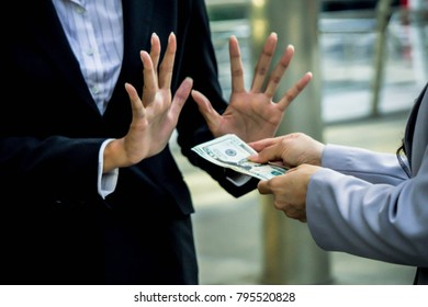 Concept of no bribe stop corruption, businessman or businesswoman  holding stack of money in hand offering bribe, hand gesture rejecting the proposal.