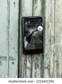 concept of obsolete technology:mobile phone nailed to the fence a large nail