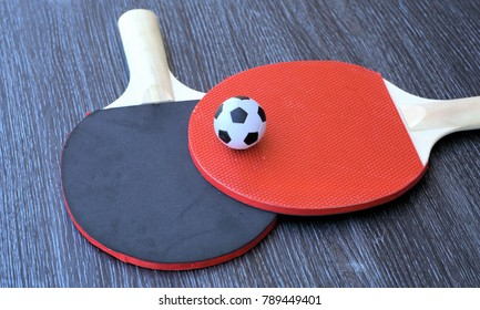 Concept of odd match with small football on table tennis rackets. Concept of odd pair with soccer ball on pig pong rackets. Unusual pairing of two different things or objects.