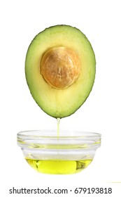 concept of oil from avocado falling in a cup with oil on it on white backgroungd