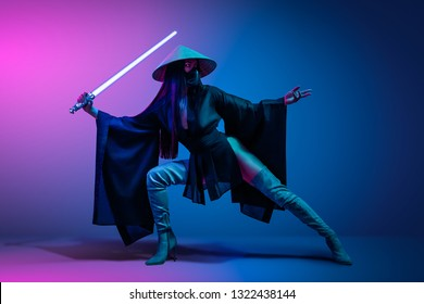 Concept on cosmic cosplay. Сontemporary portrait a young athletic woman in traditional Japanese black kimono, an Asian hat and highboots is holding a lightsaber and posing on neon blue-pink background