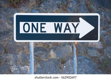 Concept One Way streetsign traffic direction with white right pointing arrow on black and dark wall as blurred background, copy space outdoor.