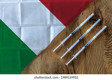 Concept of the ongoing efforts by Italy to deliver and distribute COVID-19 vaccines with three syringes on a wooden table ready to use with an Italien Flag. Copy Space for Text and Graphics.