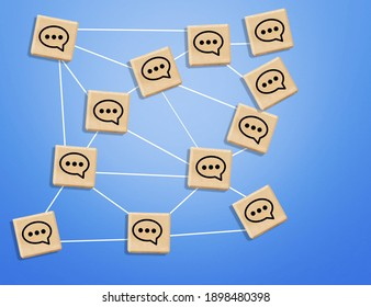 Concept of online communication or social networking. Wooden cubes with speech bubbles linked to each other with lines.