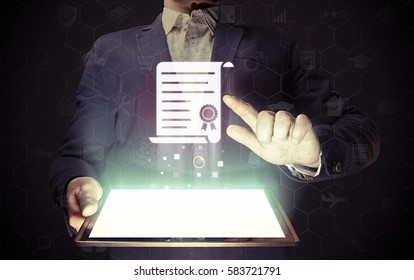 Concept of online learning. Man  touches to certificate icon  (diploma). He  holds tablet pc, that contains a many different online services.