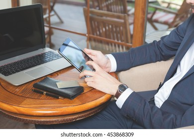 Concept of online payment by plastic card through the Internet Banking. Close-up of human hand for mobile phone and holding credit card, man pays the bill. Laptop at table