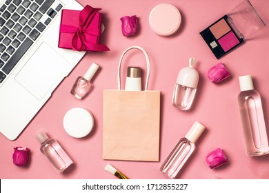 Concept of online shopping cosmetics. Top view on cosmetics bottles, cream, soap, makeup brushes, computer, paper bag on a pink background, flat lay, copy space.Layout for online cosmetics store