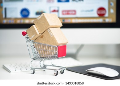 Concept of online shopping or e-commerce with miniature paper boxes on shopping trolley against computer