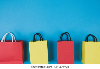 Concept online shopping with paper bag on blue paper background.