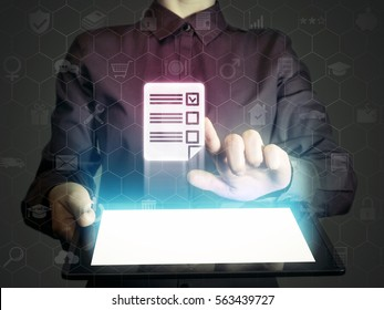 Concept of online testing, questionnaires, voting. Person (man or woman) touches to questionnaire icon. He holds tablet pc, that contains a many different online services.