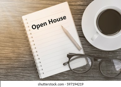 Concept Open House message on notebook with glasses, pencil and coffee cup on wooden table.