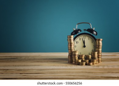 concept of Opportunity cost time is money clock and coins on wooden table