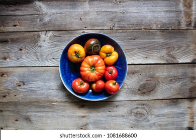 concept of organic gardening, healthy agriculture or summer food with rustic heirloom red tomatoes with cracks and imperfections over wooden table, flat lay in studio