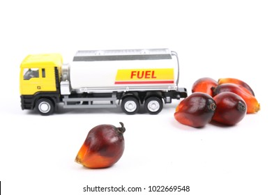 Concept of palm oil biofuel with oil palm fruitlets and toy tanker truck