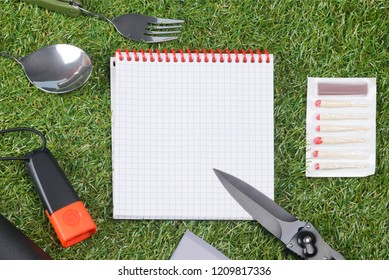 concept,  paper sheet and items for an expedition on green grass, close-up
