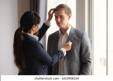 Concept partnership, couple in business. Asian girlfriend is happy to dress up for his boyfriend in the morning before he goes to work.