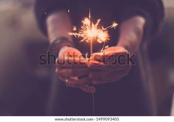 Concept of party nightlife and new year eve 2020 - close up of people hands with red fire sparklers to celebrate the night and the new start - warm colors filter - joy and hope concept life