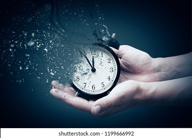 Concept of passing away, the clock breaks down into pieces. Hand holding analog clock with dispersion effect - Shutterstock ID 1199666992