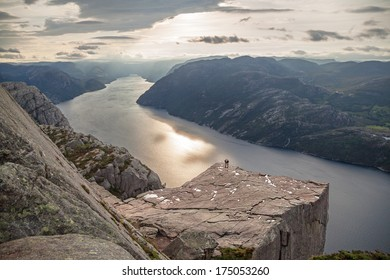 Concept people and nature; silhouettes of two people on Pulpit Rock Preikestolen, Norway.  Canon 5D.
