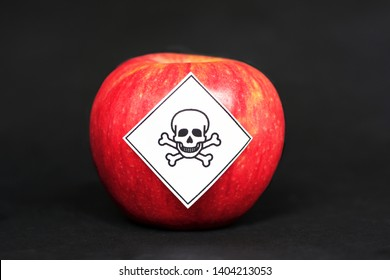 Concept of pesticide residues in agricultural food products dangerous to humans, showing a red apple with poison symbol sticker on black background