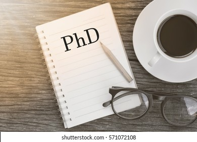 Concept PhD Doctor of  Philosophy Degree Education Graduation message on notebook with glasses, pencil and coffee cup on wooden table.