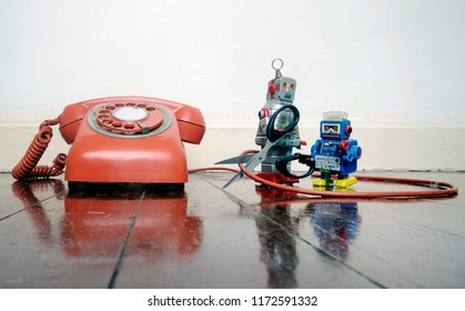 concept phone line being cut of with retro robots on a wooden floor