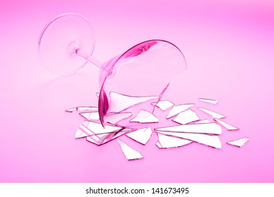 Concept photo of broken relationship with  broken martini glass and shattered mirror shot on light table with red light